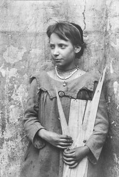 """""""I especially like this photograph of a girl holding scrap timber. It fascinates me that her clothes and jewelery demonstrate such pride in her appearance, even while her hands are dirty and she is collecting firewood. It is obvious that Horace Warner never asked his subjects to smile, instead he granted them the space for self-possession and she presents herself on her own terms, with composed equanimity and preoccupied in her world."""""""