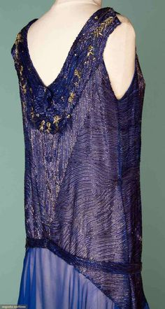 COBALT BEADED GOWN, 1930s Blue silk chiffon covered in serpentine rows of dark blue bugle beads, diamante blossoms around neckline, below knee chiffon skirt, back neckline w/ low V beaded collar, matching belt. Sideway