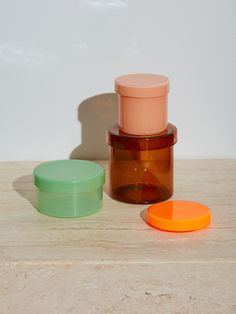 "Simple and elegant borosilicate glass containers with lids by HAY. Perfect for your cotton swabs, cotton balls, etc. in your bathroom or any other petite storage needs. Neon Orange, Pink, or Blue, Extra Small: .75"" H x 3.25"" DIA Peach, Brown, or Cherry Red, Small: 2.76"" H x 2.95"" DIA Mint, Medium: 1.97"" H x 3.74"" DIA Brown, Large: 3.74"" H x 3.74"" DIA --NOTES--We absolutely love these little containers in our bathroom."