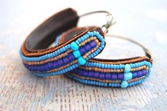 Lovely idea: beaded embroidered earrings on leather. Turquoise and lillac tones.