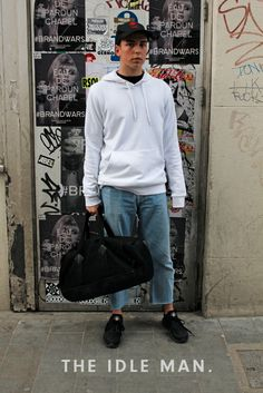 Men's street style | Weekender - If you're going on weekend break, then this is an ideal look for you. Layer up a hoodie and crew neck tee, then pair it up with light wash jeans and black trainers. Finish it all off with a cap for the laid-back look. | Shop the look at The Idle Man