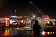 Newport News Fire Department responds to the scene of a fire at Hall Acura at 12501 Jefferson Ave as bystanders watch Friday evening. (Jonathon Gruenke / January 10, 2014)