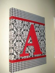 Start with a canvas and mod pod fabric or scrapbook paper.  Add ribbon. Paint a cardboard letter and add.