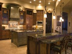 Very warm, comfortable kitchen design. The granite counters really complement the tone of the wood, and I like the soft lighting. Might have more pendant lamps and less recessed lighting, but overall this is one of my favorite kitchen designs.