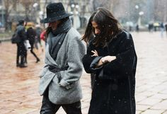 Emmanuelle Alt in a belted grey coat + black leather trousers + grey scarf + black wide-brim hat and Capucine Safyurtlu in a black coat