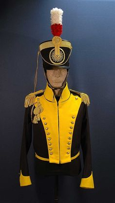 "19th Light Dragoon Trooper, 1814. The ""New Pattern"" uniform consisted of a black felt shako with a band of worsted lace in the regimental lace colour edging the top, a black wheel edged in the lace colour in front, white over red plume, yellow cords and tassels, and brass chinscales. Blue coatee with collar, cuffs, lapels, turnbacks and piping at the back seams and sleeves of the regimental lace colour. (Image: historicaltwiststore.com)"