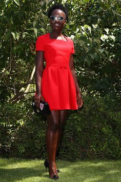 Lupita Nyong'o wears a bright red Dior dress, Dior sunglasses, pumps and a clutch