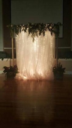Beautiful wedding backdrop | tulle | christmas lights | greenery | love | winter wedding | woodland | @TaylorPhillippe