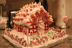 Gingerbread House Peppermint Lane - decorated with peppermint lollipops, candy cane pretzels, candy cane Hershey's kisses, crushed peppermint candies, gumdrops, shredded coconut for the snow