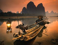 Guilin, China: A cormorant fisherman showed me his traditional fishing methods ( > 1000 yrs. old). They fish at night, their lantern attracts fish, & the cormorant dives in to catch them.   I asked if I could photograph him & used a fill flash to keep the wing detail in the black Cormorant. Suddenly it spread it's wings, & then It held them open for about 2 seconds.  That single moment, was the key to the entire image.