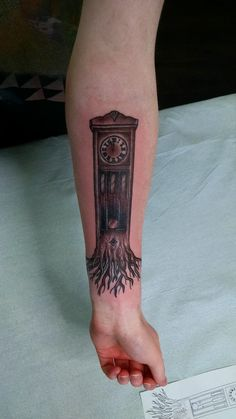 Family heirloom timepiece grandfather clock tattoo with roots that represent family.
