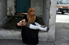 A mother in Gaza carries her child home after being treated in the hospital. Their home was bombed by Israel.