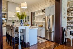 Andrea Drake and Tracy Frye gave this small kitchen a dash of country charm through the use of open shelving, knickknack displays and rustic wood-plank walls.