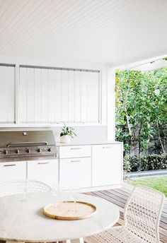 **Outdoor kitchen** Marine ply cabinetry with a Caesarstone top was custom-designed by [Vitale Design]. A round marble table from Blu Dot and Vela chairs from Cosh Living sit atop the spotted gum decking. Indoor Outdoor Living, Outdoor Areas, Outdoor Rooms, Outdoor Dining, Outdoor Bbq Kitchen, Outdoor Kitchen Design, Spotted Gum Decking, Fresco, Les Hamptons