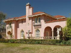 Pink stucco is a common exterior choice for the Mediterranean style home. Clay roof tiles are often used in warmer regions both to add beauty and keep the home cool. Angel statues an ornate concrete fence border greet guests and create a sense of luxury and elegance to the front space.