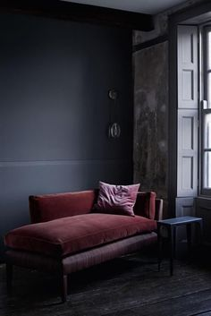 Rich dark velvet lounger ; dark walls ; celestial pebble wall light ; moody room