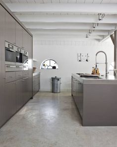 really love the 'industrial' look of this kitchen; smooth grey cupboards, exposed ceiling beams, and polished concrete floors. yes, yes, yes!