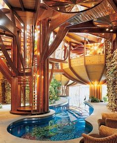 "An incredible home in  Columbus Ohio with A 75-foot-long pool that winds its way through the lower level of the house. ""The owner wanted a lap pool running through a tropical garden, with palm trees and bananas and views of the sky,"" the architect says. ""The living spaces are arranged around that."""
