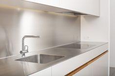 Küche mit Edelstahlabdeckung, weiss lackierten Fronten und Schubladen in Eiche massiv
