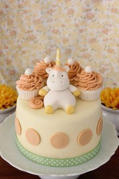 Light yellow Unicorn cake with cupcake toppers