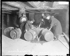 Small group of men in the process of dumping wine from barrels into a hole in the ground  in a warehouse during Prohibition in Chicago, Illinois, 1921.