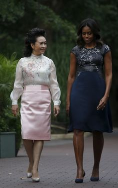 A demure look for Ms Peng Liyuan (left), who pairs a floaty white blouse with pink floral motifs with a satin pink skirt, as she and US First Lady Michelle Obama announce the name of the giant panda cub, Bei Bei, at the Smithsonian National Zoo.