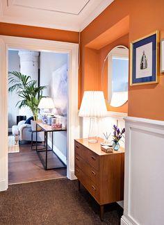Eteisen galleriakäytäväksi ristitty käytävä johtaa olohuoneeseen. Lipasto on osto- ja myyntiliikkeestä ja Maire Gullichsenin suunnittelema valaisin on Artekista.
