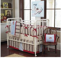 Sock monkey baby bedding set with a baby blue, brown and red striped quilt bumper pad and fitted crib sheets and striped mattress ticking bed skirt with gray stripes for an airplane theme nursery