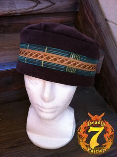 """This is what I call the """"gypsy"""" hat. This design I created when building a gypsy outfit. The hat is made from a Brown Linen. The brim has green ribbon trim around it, with a printed brown ribbon on top of that. It is fully lined and has denim as interfacing to make it more durable. It measures 24.5"""" on the inside."""