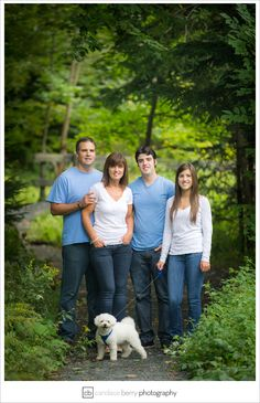 The background is good, the lighting behind the family helps them to stand out against the dark greenery. Family of four with teens.