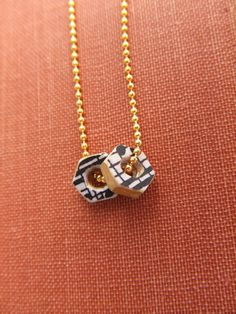 Industrial chic! This pendant is made from two brass hex nuts and sheet music. Beautiful and golden!