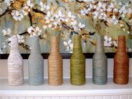 Empty beer bottle vases wrapped in yarn.