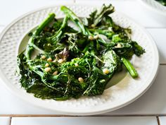 Roasted broccoli rabe is mellower than its sautéed twin - an easy side dish that goes with anything. Brightened with lemon zest and topped with pine nuts.
