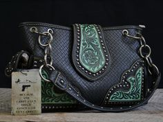 Genuine leather bag from Montana West. Black leather, silver grommets, and blue/teal accents in tooled leather. Concealed carry pocket on the back; two side pockets; many inside compartments.
