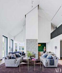 The living room of film and TV producer Brian Grazer's modern, Santa Monica, California, mansion, with interior design by Waldo Fernandez, features triangular chairs by Rick Owens and a painting by Richard Prince.
