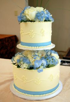 Scrollwork and blue ribbons, plus lovely flowers, make a simple cake beautiful.