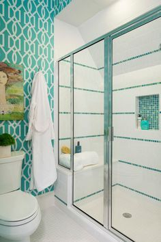 Fabulous girl's bathroom features turquoise trellis wallpaper on walls framing a large chrome and glass shower boasting an oversized subway tiled surround accented with stripes of turquoise mosaic tiles over a turquoise mosaic tiled shower niche and built-in shower bench atop white grid tiled floors which continue into the bathroom.