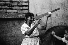 Magnum Photos - Larry Towell San Salvador. 1986. Mejicanos neighbourhood. While her grandchild looks on, an elderly woman palys with a toy gun during the war in El Salvador.