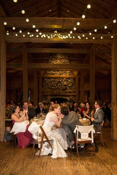 devils thumb ranch, winter mountain wedding, bride and groom kissing after toasts, reception, market lights, log cabin