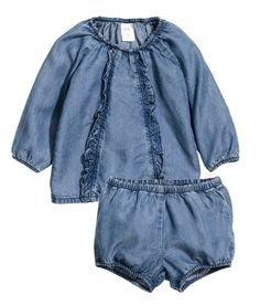 BABY EXCLUSIVE/CONSCIOUS. Een blouse en een pofbroekje van zacht, gewassen denim van Tencel® lyocell. De blouse heeft volants voor, lange raglanmouwen en elastiek langs de halsopening. Het broekje heeft elastiek in de taille en onder aan de pijpen.