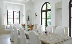 Dark stained windows contrast nicely against white walls, slipcovered chairs.