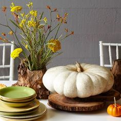 This Thanksgiving centerpiece is all about natural beauty: wood, an heirloom pumpkin, flowers. Details + more ideas for Thanksgiving centerpieces: http://www.midwestliving.com/homes/seasonal-decorating/holiday-ideas/easy-thanksgiving-centerpieces/page/13/0