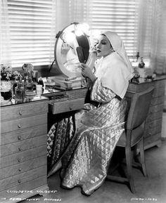 Claudette Colbert applies makeup at her dressing table.