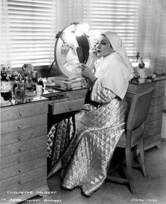 Claudette Colbert applies makeup at her dressing table.