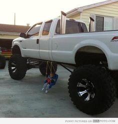 Big car advantages - Funny kid swinging on a swing hanging under a big truck.