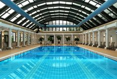 Fabulous Huge Indoor Pool Idea with Rectangular Shape and Tiled Pools and Nice Lounge Chairs also White Pillars Decorations and Brown Floor Tile and Stunning Glass Ceiling Idea