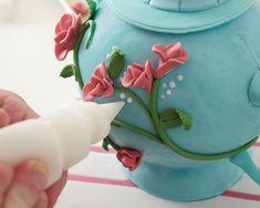 <h5>Encha um saco de confeitar com glacê real e preencher o espaço em branco em torno das flores e na borda da tampa e da base. Cole a uma fita em torno da borda da placa para terminar.</h5>
