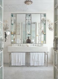 I love the high ceilings, sink, and large-scale mirror, with built in shelving. The intricate sconces are also quite beautiful. The white and grey color palette is perfect for a master suite—fresh and serene.