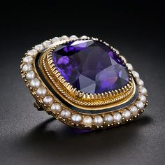 This modestly sized, but thoroughly lovely, high-quality adornment for your blouse or lapel features am entrancing, deep and radiant purple cushion-cut amethyst. The gemstone is securely embraced by no less than (let's say, numerous) prongs, and is outlined with a subtle border of black enamel and a lustrous frame of tiny natural seed pearls. This endearing and enduring antique jewel, circa 1860, measures 13/16 inch in diameter. 15 karat gold, hence most likely of British origin.