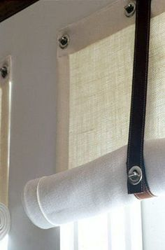 Sailcloth curtains hung with rivets and and tied with top stitched leather fittings.